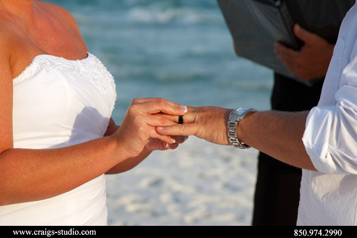 Brenda giving Brian his ring in a beach wedding in Destin, Florida